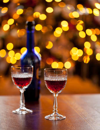 sherry: Cut glass sherry or port glasses in front of an out of focus christmas tree with blue bottle