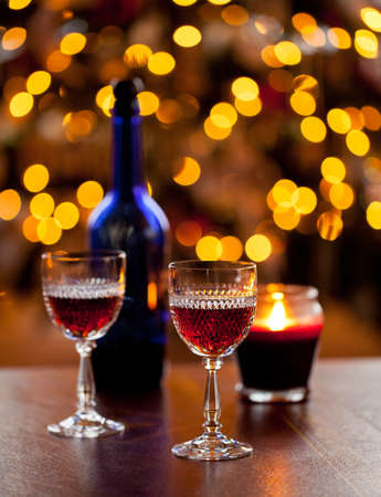 Cut glass sherry or port glasses in front of an out of focus christmas tree with blue bottle photo