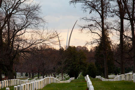 Christmas wreaths on gravestones in Arlington National Cemetery. Air Force memorial soars in the distance as the sun sets at dusk