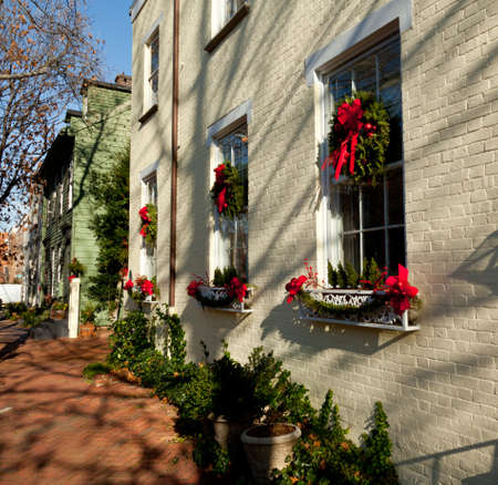 Old brick colonial house decorated for Christmas with wreath on door photo