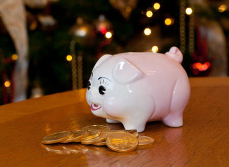 bank branch: Pink piggybank on a wooden table in front of a christmas tree with gold coins Stock Photo