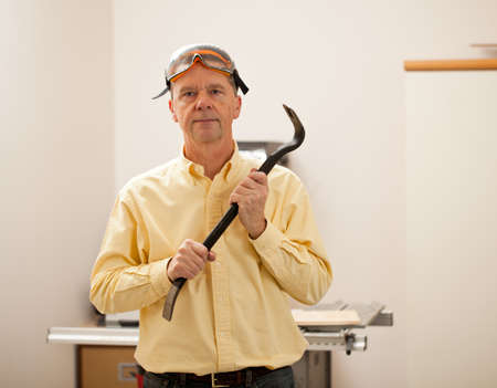 Senior male in a home workshop facing the camera and holding a crowbar Stock Photo - 11781674