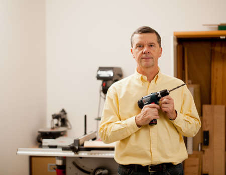 Senior male in a home workshop facing the camera and holding a power drill Stock Photo - 11781710