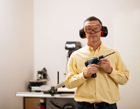 Senior male in a home workshop facing the camera and holding a power drill Stock Photo - 11781712