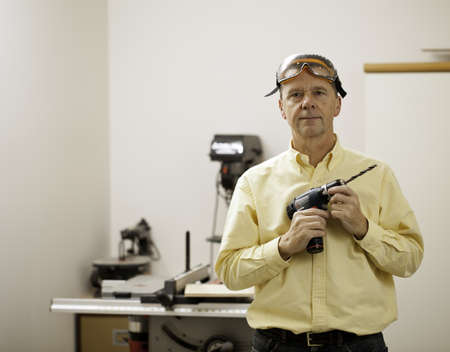 Senior male in a home workshop facing the camera and holding a power drill Stock Photo - 11781719
