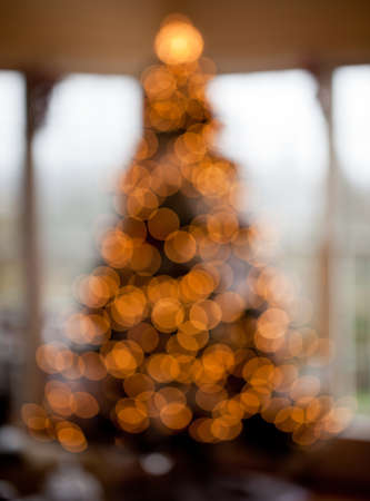 Deliberated blurred Christmas tree decorated with silver and white ribbons to get the out of focus images of the lights in family home Stock Photo - 11781715