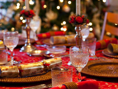 Christmas crackers on table set for Christmas lunch with candles and tree in background photo