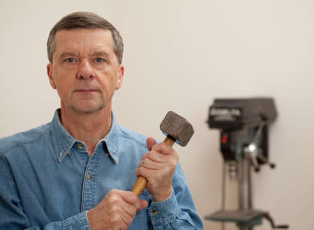Senior male in a home workshop facing the camera and holding a large lump hammer Stock Photo - 11781818