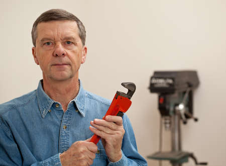 Senior male in a home workshop facing the camera and holding a large wrench photo