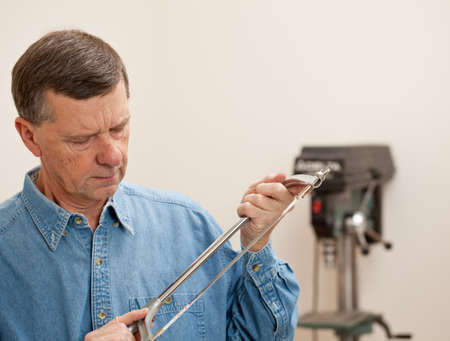Senior male in a home workshop facing the camera and holding a metal saw Stock Photo - 11781817