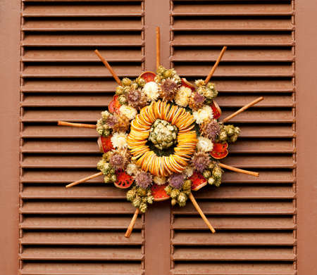 Traditional design of a christmas wreath attached to the front door of old house photo