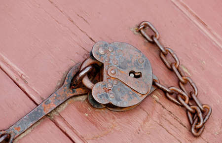 Rusty old padlock and chain fastening a door opening photo