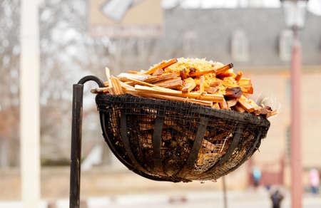 log basket: Basket for kindling used to light a street at night