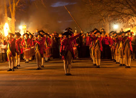 christmas military: WILLIAMSBURG, VIRGINIA - DECEMBER 29: Marching soldiers at night on December 29, 2011. Colonial Williamsburgs 301 acres includes many restored buildings and houses and hosts re-enactments.