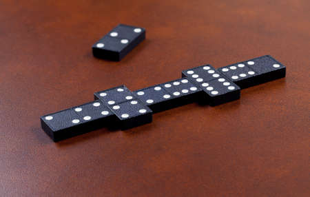 dominoes: Macro image of dominos on a leather table in the middle of a game Stock Photo