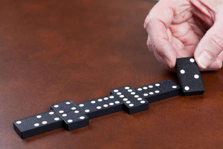 dominoes: Macro image of dominos on a leather table in the middle of a game with hand placing a tile