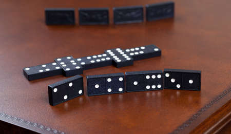 Macro image of dominos on a leather table in the middle of a game Imagens