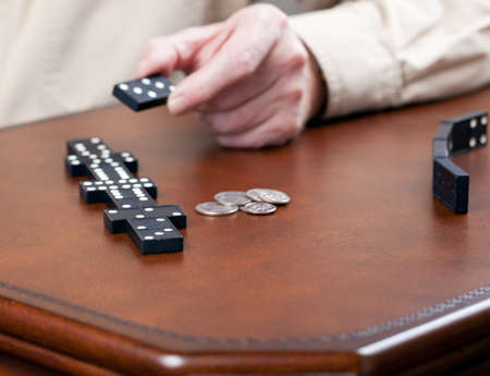 Macro image of dominos on a leather table in the middle of a game with hand placing a tile