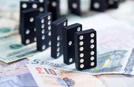banking crisis: Standing dominoes on pound, euro and dollar bank notes illustrating banking crisis