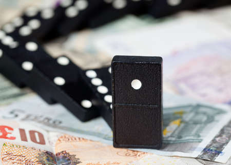 Fallen dominoes on pound, euro and dollar bank notes illustrating banking crisis Stock fotó