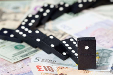 global crisis: Fallen dominoes on pound, euro and dollar bank notes illustrating banking crisis Stock Photo