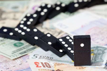 banking crisis: Fallen dominoes on pound, euro and dollar bank notes illustrating banking crisis Stock Photo