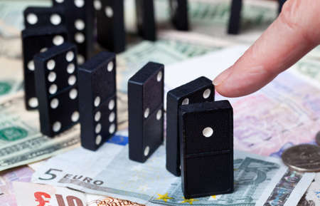 global currencies: Finger pushing standing dominoes on pound, euro and dollar bank notes illustrating banking crisis Stock Photo