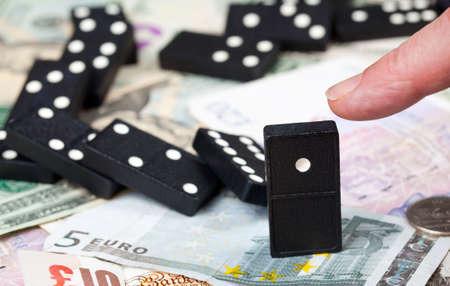 banking crisis: Finger pushing last domino standing on pound, euro and dollar bank notes illustrating banking crisis Stock Photo