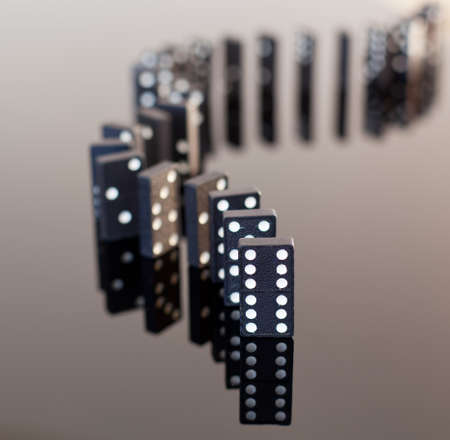 dominoes: Macro image of dominos on a black reflactive surface and standing in a row