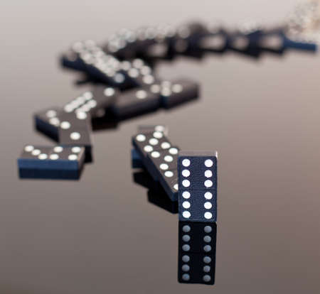 dominoes: Macro image of dominos on a black reflactive surface and collapsed in pile