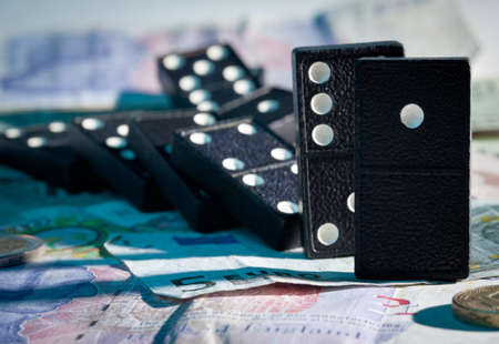 banking crisis: Fallen dominoes with blue harsh shadows on pound, euro and dollar bank notes illustrating banking crisis