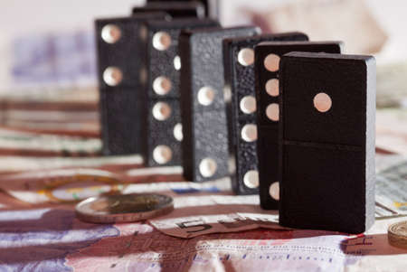 global crisis: Standing dominoes with harsh shadows on pound, euro and dollar bank notes illustrating banking crisis