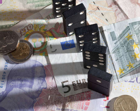 banking crisis: Standing dominoes with harsh shadows on pound, euro and dollar bank notes illustrating banking crisis