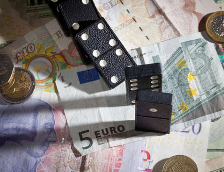 banking crisis: Fallen dominoes with harsh shadows on pound, euro and dollar bank notes illustrating banking crisis Stock Photo