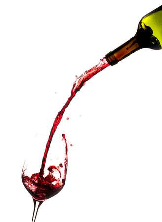 Rode wijn wordt direct gegoten uit de fles in een grote beker Stockfoto