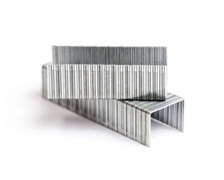 Two rows of paper staples lying on top of each other and isolated in white Stock Photo - 11977482