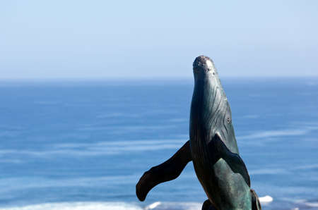 breaching: Bronze statue of whale breaching from  sea with ocean in the background
