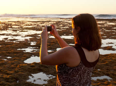 sidelit: Photographer using smartphone to take a picture of setting sun Stock Photo
