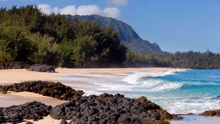 na: Waves crash onto Lumahai beach on Kauai Hawaii with Na Pali Coast Stock Photo