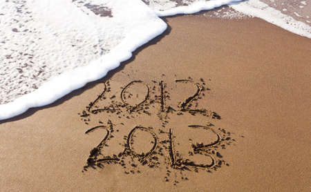 2012 and 2013 written in sand on beach with sea waves starting to erase the word Stock Photo - 12451475