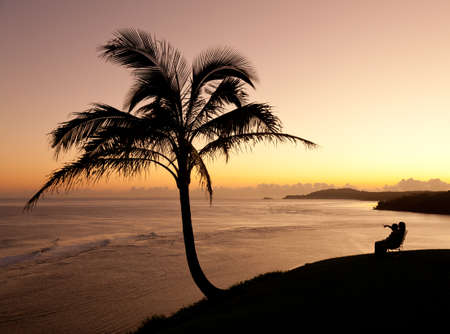 Sunrise with couple between two palm trees and looking towards Kilauea lighthouse photo