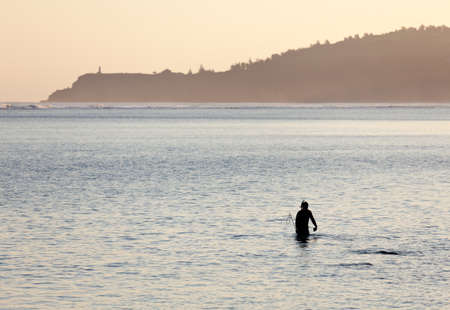 Silhoutted snorkling man on beach in Kauai at sunrise photo
