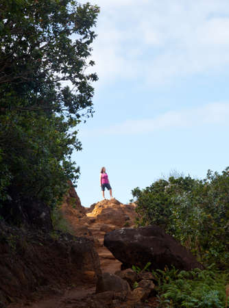 gazing: Single woman walker on summit of Kalalau trail along Na Pali coast in Kauai Hawaii Stock Photo