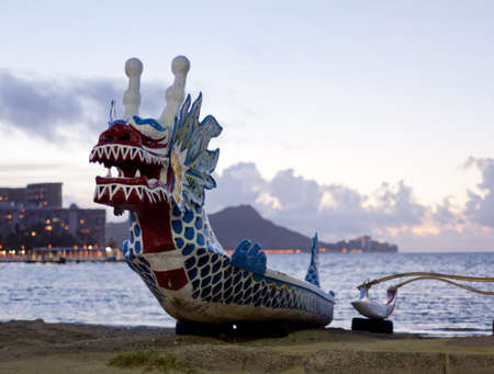 Dragon shaped head on traditional canoe on sand in Waikiki with Diamond Head Stock Photo - 12451406