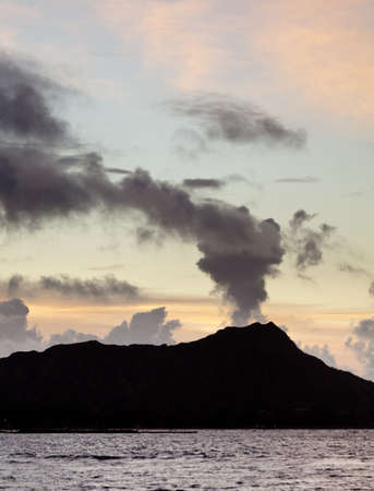 diamond head: Clouds appear to be smoke from volcano of Diamond Head at sunrise in Hawaii