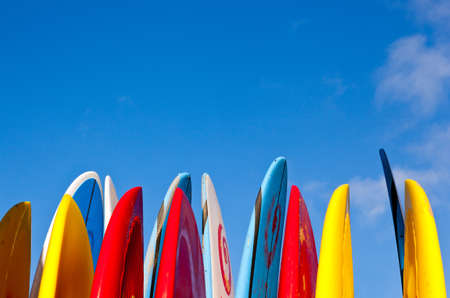surfboard: Set of different color surf boards in a stack by ocean