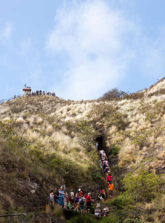 the height of a rim: Waikiki, HI - JANUARY 15: Tourists climbing to summit of Diamond Head crater on January 15, 2012. The path gains 560 feet from the crater floor.