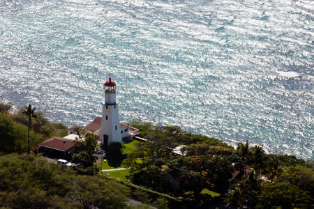 Lighthouse on coast under the summit of the old volcano of Diamond Head photo