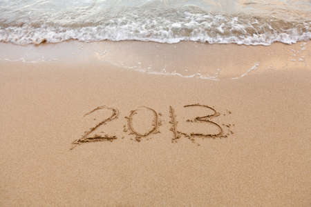 2013 written in sand on beach with sea waves starting to erase the word