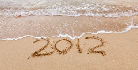 2012 written in sand on beach with sea waves starting to erase the word Standard-Bild